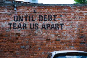 A Debt related quote on a brick wall | Debt Financing vs Equity Financing