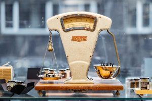 Debt Financing vs Equity Financing illustration on a weighing machine